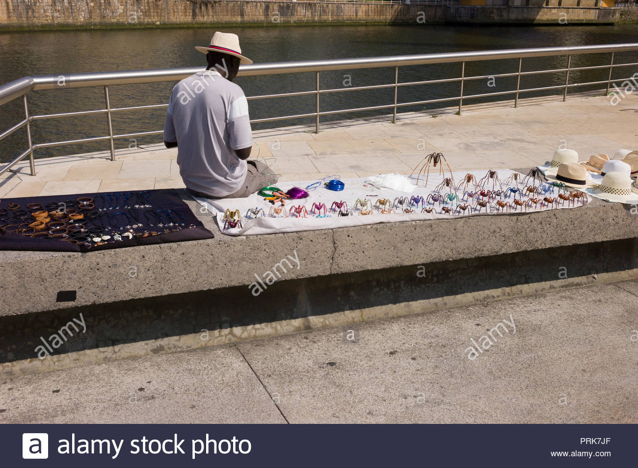 Street vendor making and selling his hand made models of the spider sculpture at the Guggenheim Museum in Bilbao, Spain Stock Photo