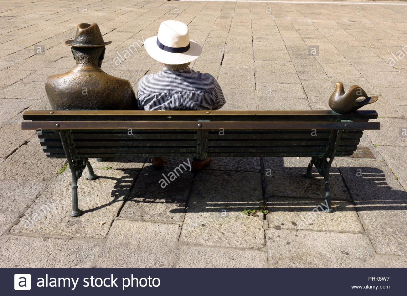 Senior male tourist sitting next to a sculpture of Antoni Gaudí opposite the Casa Botines that he designed Stock Photo