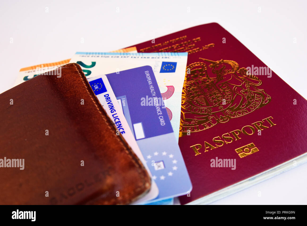 European Union United Kingdom of Great Britain and Northern Ireland burgundy biometric passport with Euro cash notes, EHIC card and driving licence Stock Photo