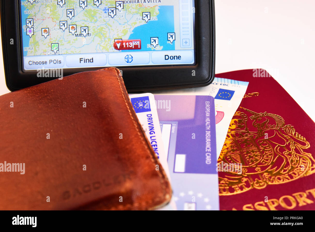 Satnav for Spain with EU United Kingdom of Great Britain and Northern Ireland biometric passport with Euro cash notes, EHIC card, driving licence Stock Photo