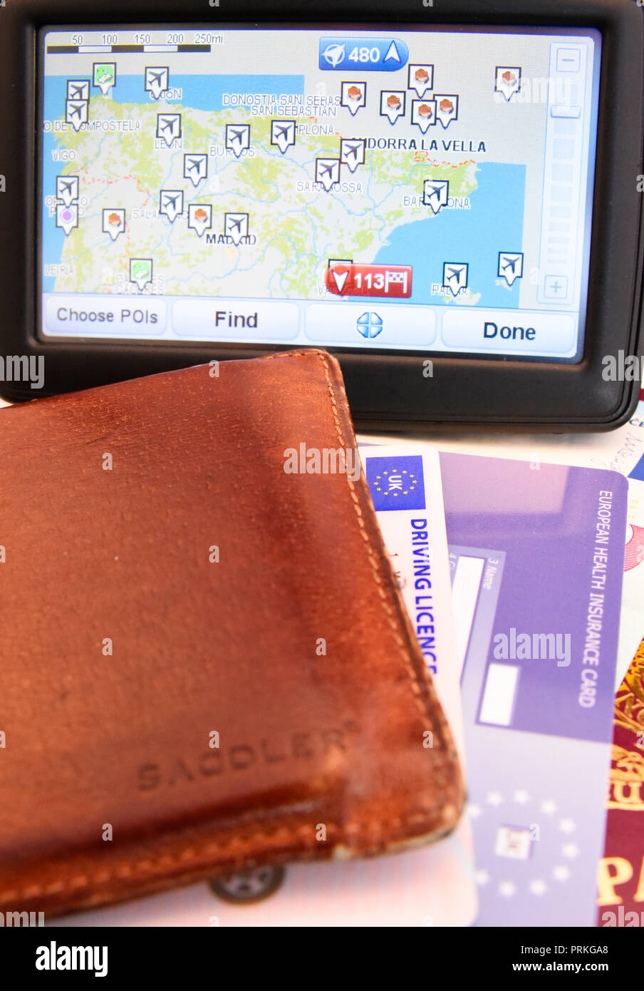 Satnav for Spain with EU United Kingdom of Great Britain and Northern Ireland biometric passport with Euro cash notes, EHIC card, driving licence - Stock Image