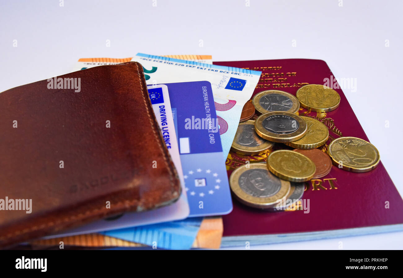 European Union United Kingdom of Great Britain and Northern Ireland biometric passport with Euro cash notes and coins, EHIC card, driving licence Stock Photo
