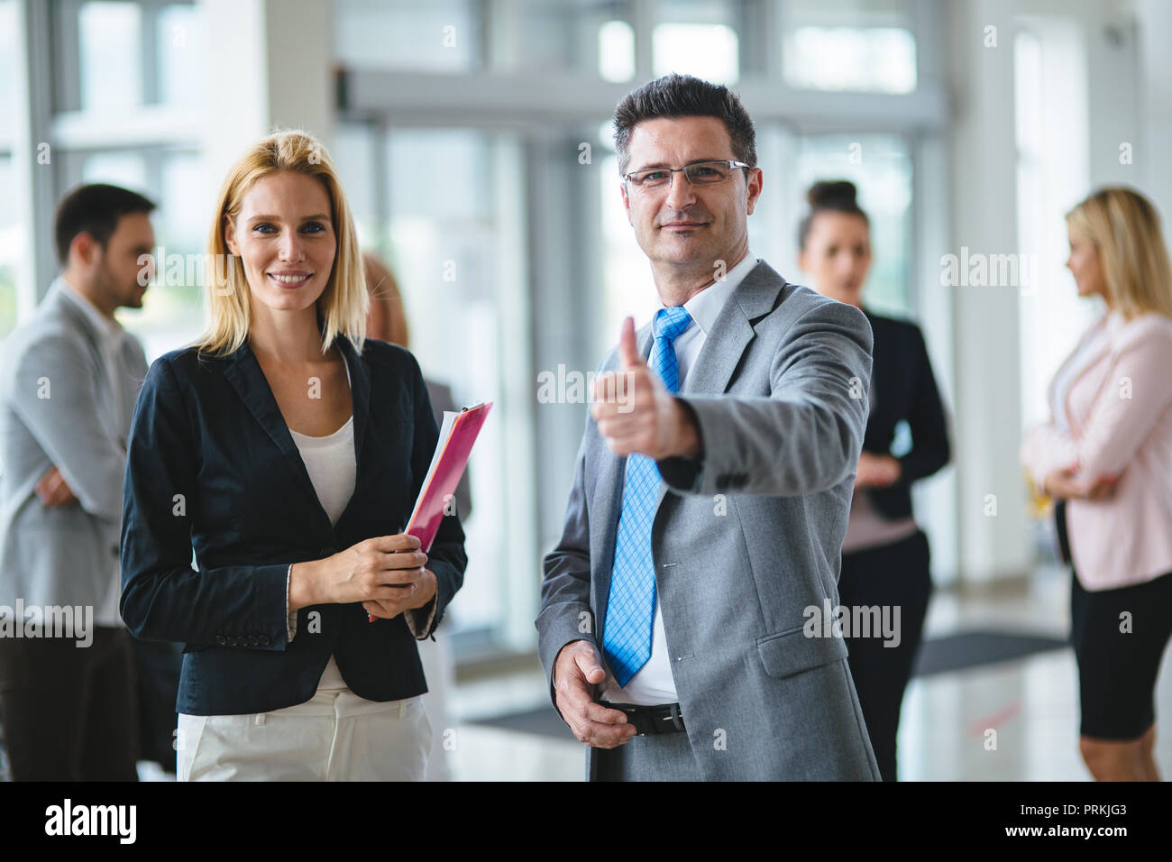 Smiling business team standing while giving thumbs up at new car showroom - Stock Image