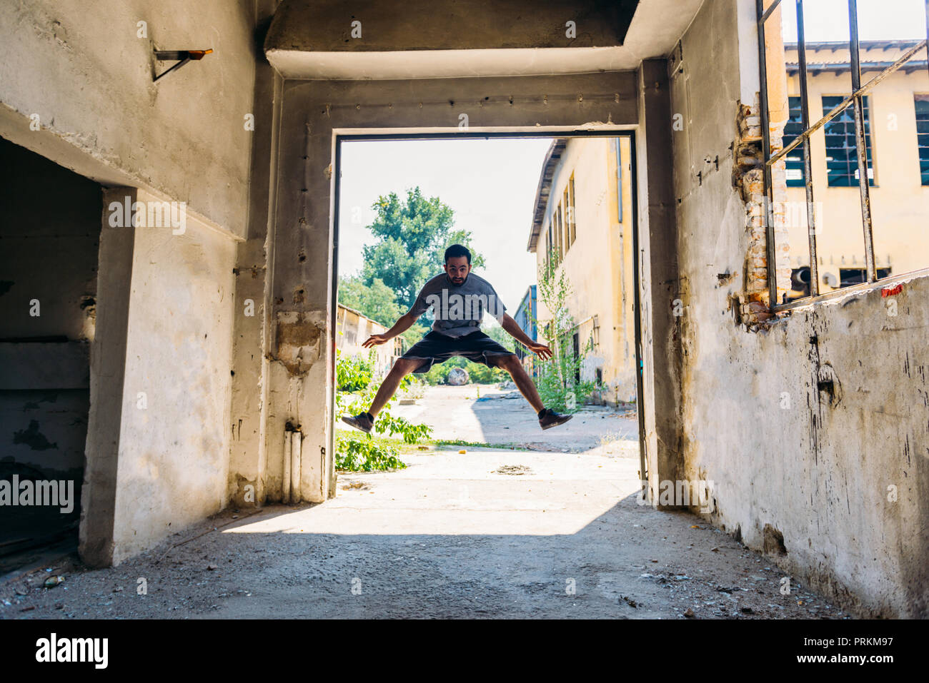 Parkour guy training parkour while jumping outdoors - Stock Image