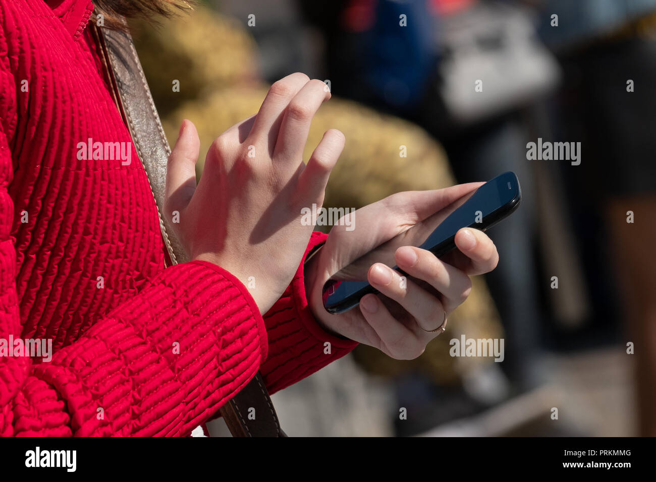The cut-off girl's photo fingers dialing number on phone. - Stock Image