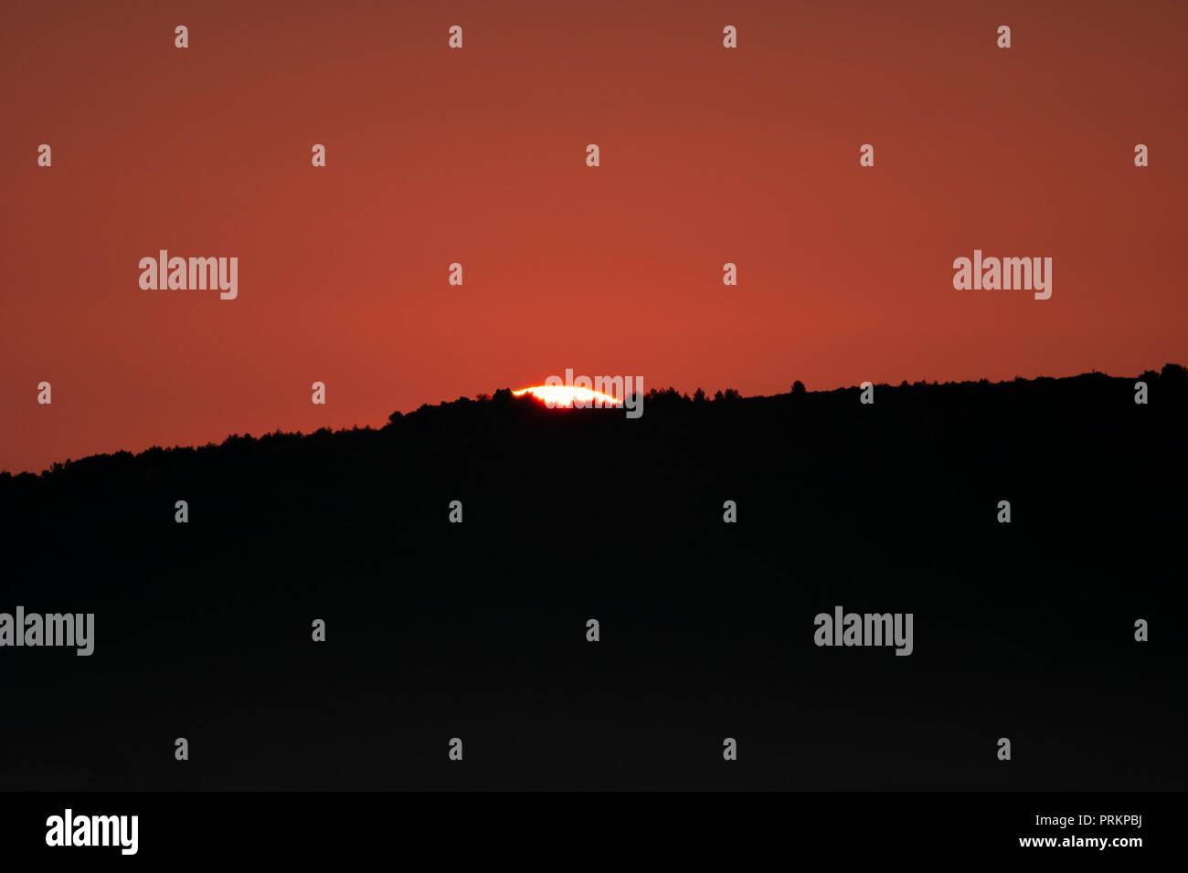 Sun rising behind the dark mountain a little bit - Stock Image