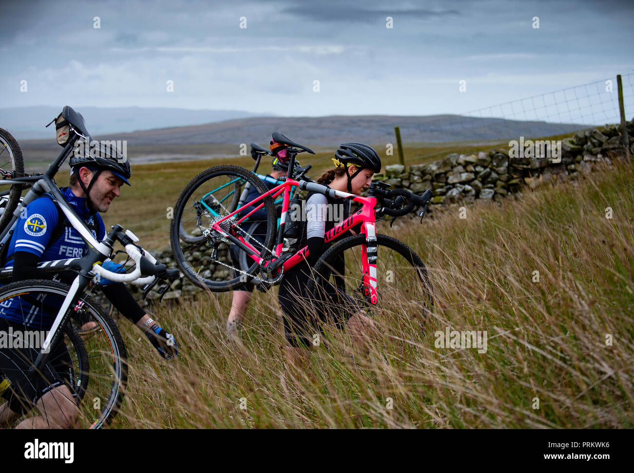 A female competitor leads part of the field up Simon Fell in the 3 Peaks cyclocross 2018. - Stock Image