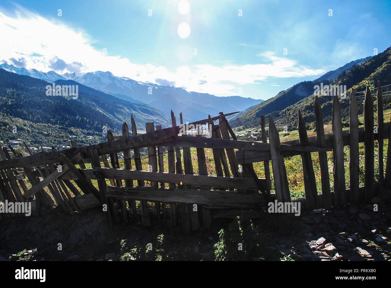 Crooked wooden fence on a sunny mountain landscape in Mestia, Svaneti, Georgia Stock Photo