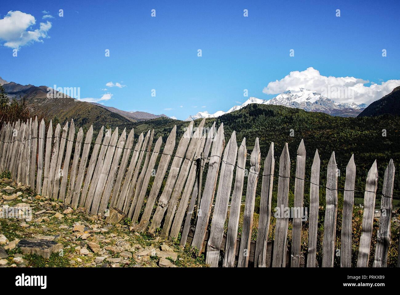 Crooked wooden fence on a mountain landscape in Mestia, Svaneti, Georgia - Stock Image