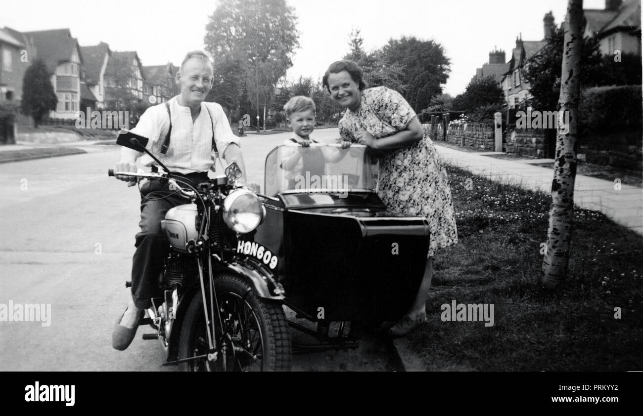 Man,woman & young boy in sidecar of a 1939 BSA M20 motorcycle combination in a residential road circa 1940 - Stock Image