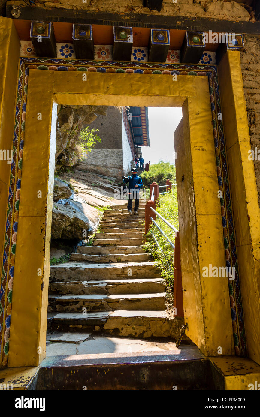 An ornate yellow coloured gate at the entrance of the Tiger's nest in the town of Paro in Bhutan - Stock Image