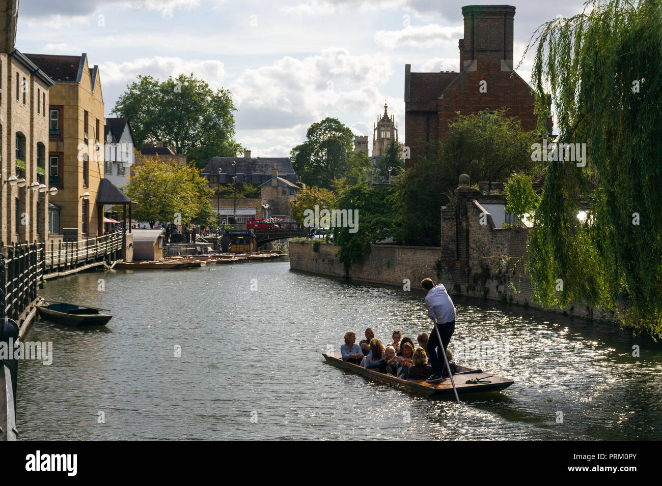 A punt boat with several people aboard on the river Cam heading to Magdalene Bridge on a sunny Summer afternoon, Cambridge, UK - Stock Image
