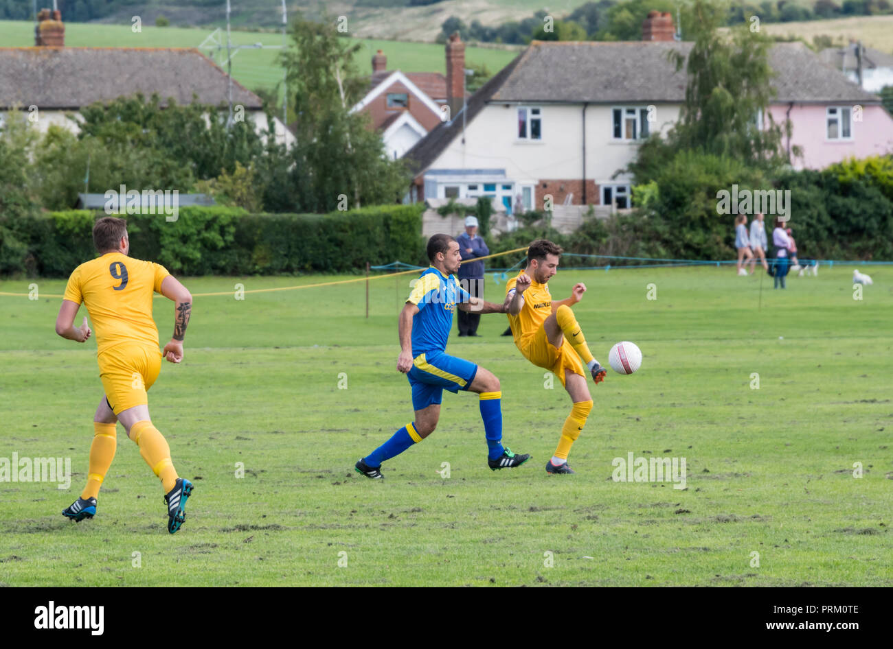 Players kicking a ball during a Saturday league football match with local amateur teams in West Sussex, England, UK. - Stock Image