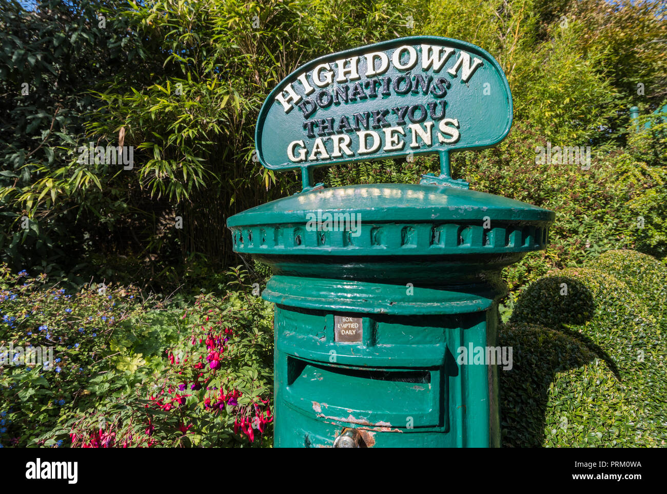 Old Royal Mail Pillar Box painted green and used for donations to Highdown Gardens in West Sussex, England, UK. - Stock Image
