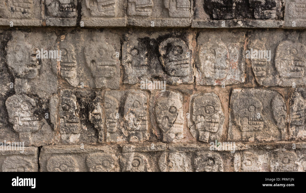Skulls carved into the walls at Mayan site, Chichén Itzá in the Yucatan Peninsula, Mexico - Stock Image