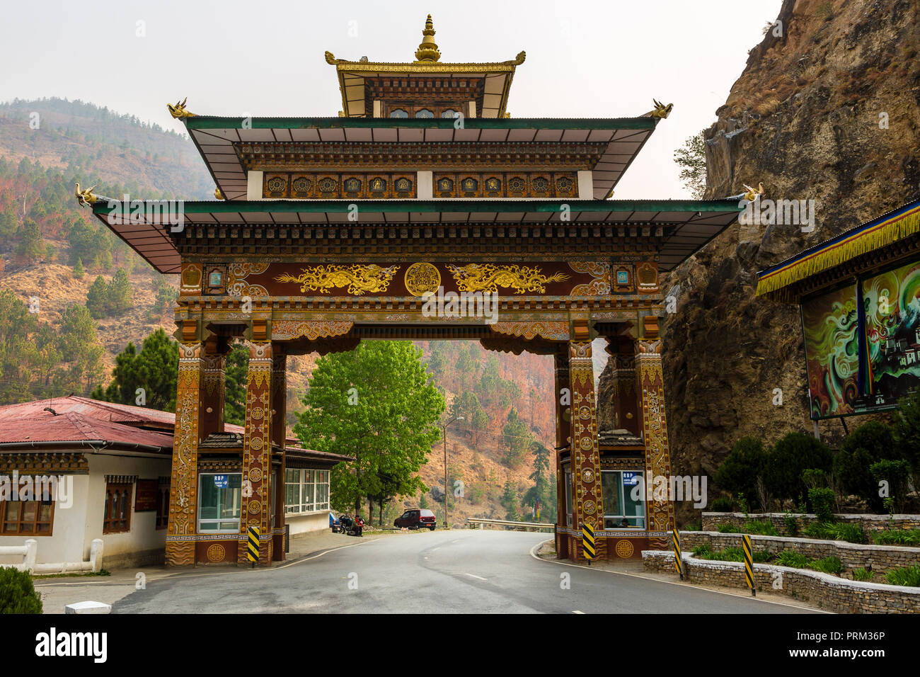 A colourful gate with ornate design on a highway road in Bhutan - Stock Image