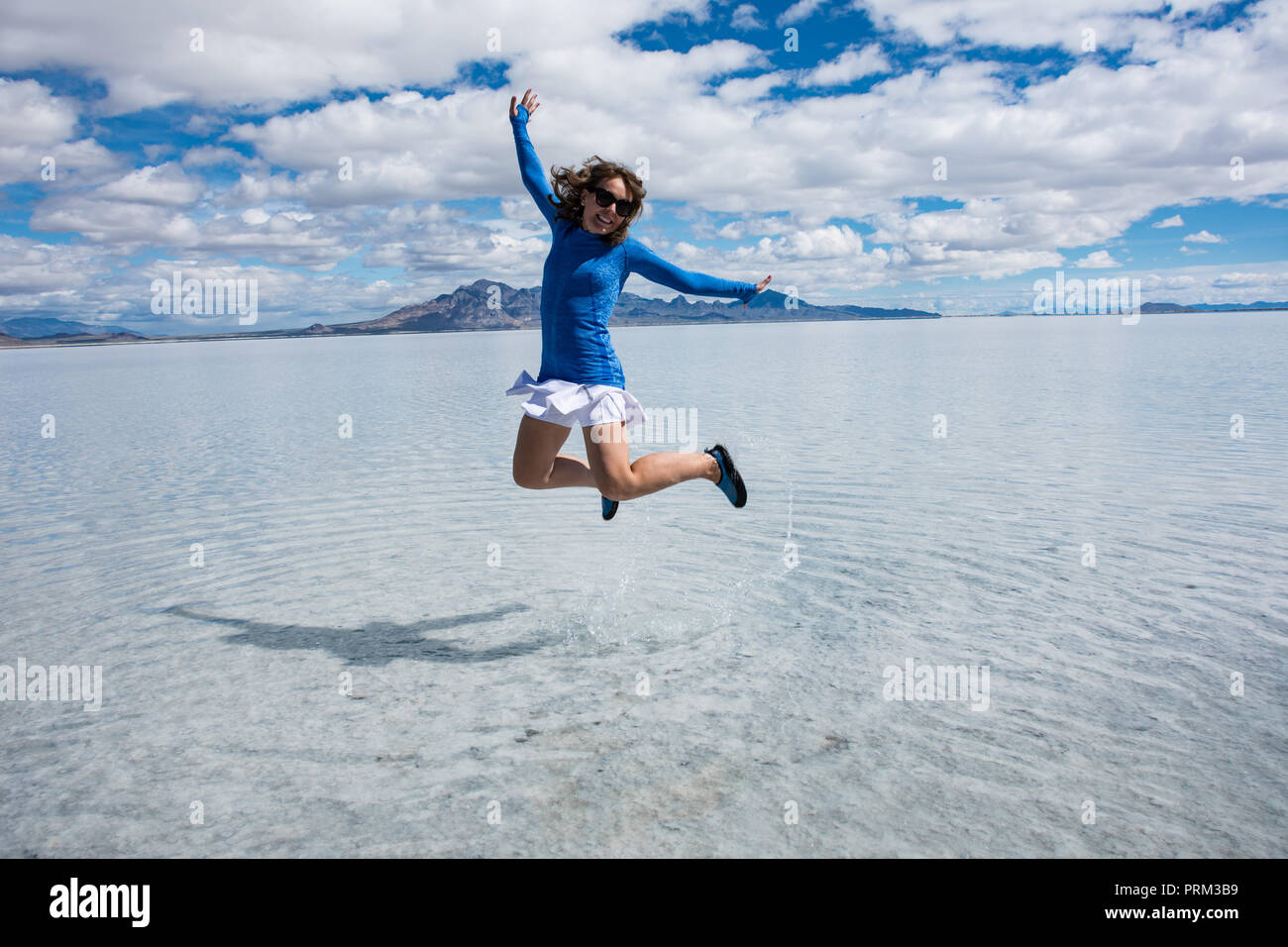 A woman jumps at the Bonneville Salt flats when the salt flats are flooded in the spring. Stock Photo