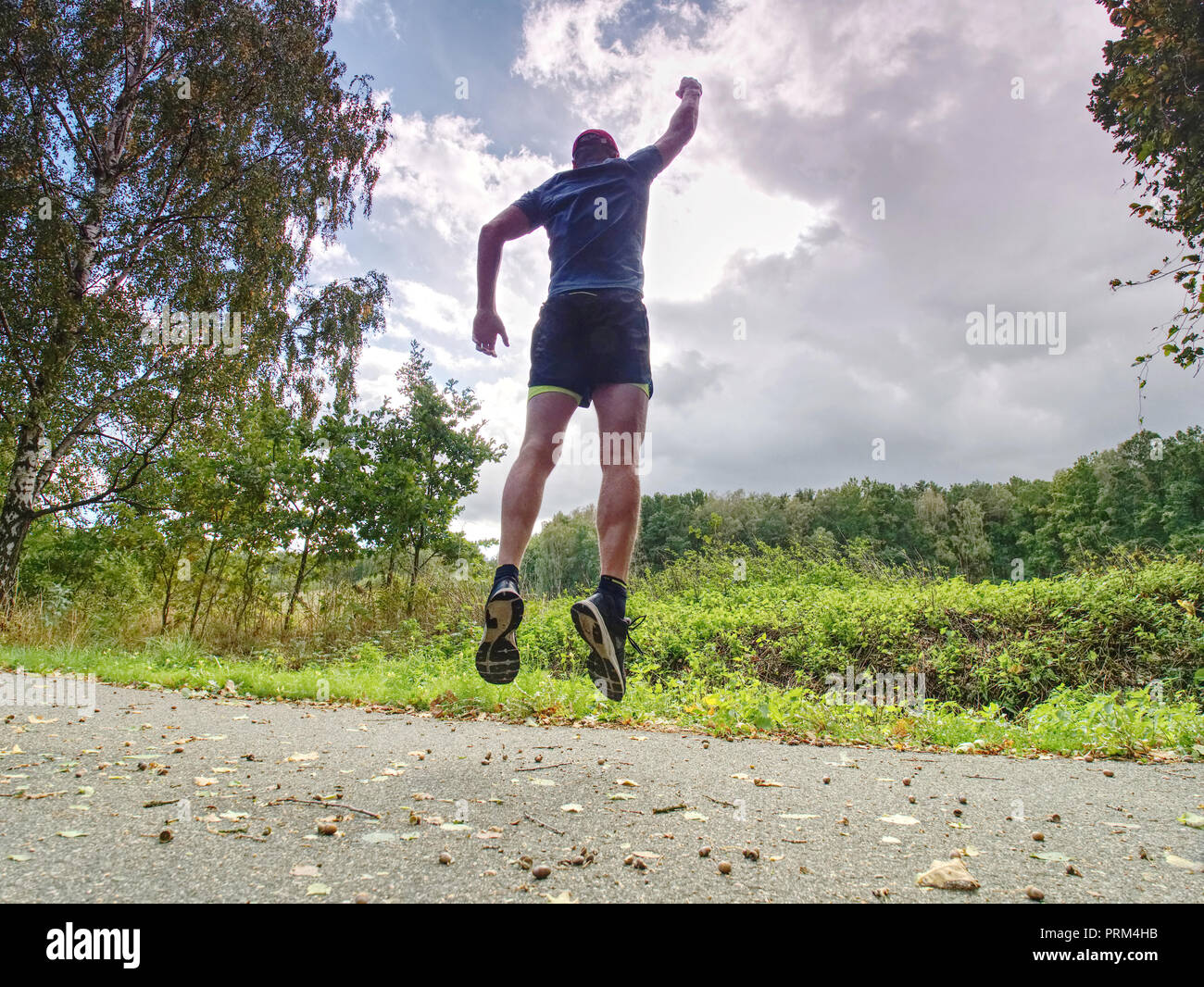 Attractive and tall runner man in slim sportswear running and training on jogging outdoors workout in city park with trees and yellow leaves - Stock Image