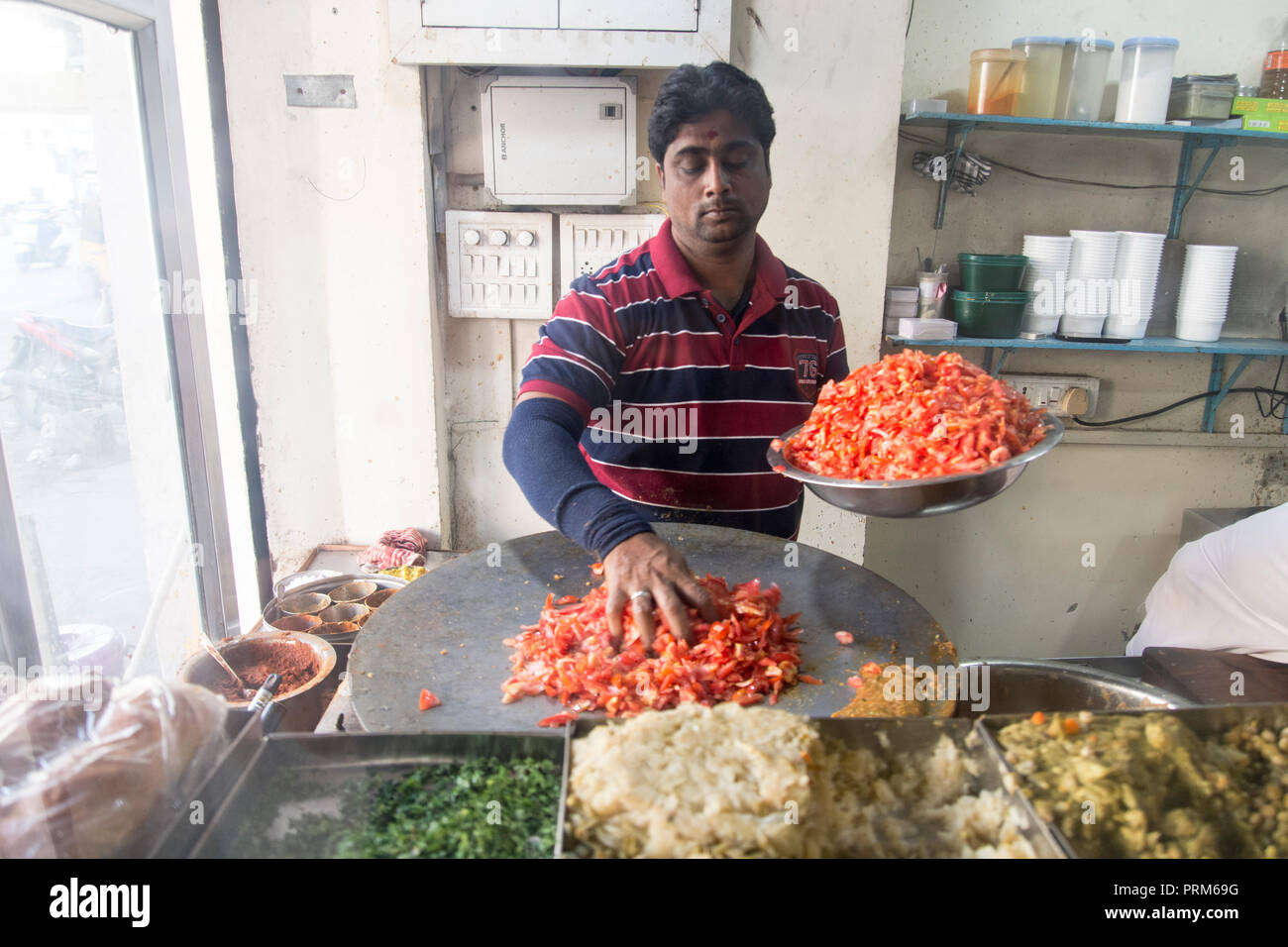 Preparing and selling Indian street food in a food stall. Photographed in Ahmedabad, Gujarat, India - Stock Image