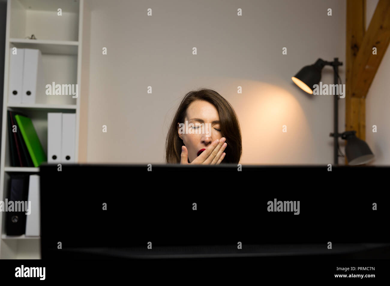Young pretty woman tired and exhausted of work next to computer. Working late concept - Stock Image