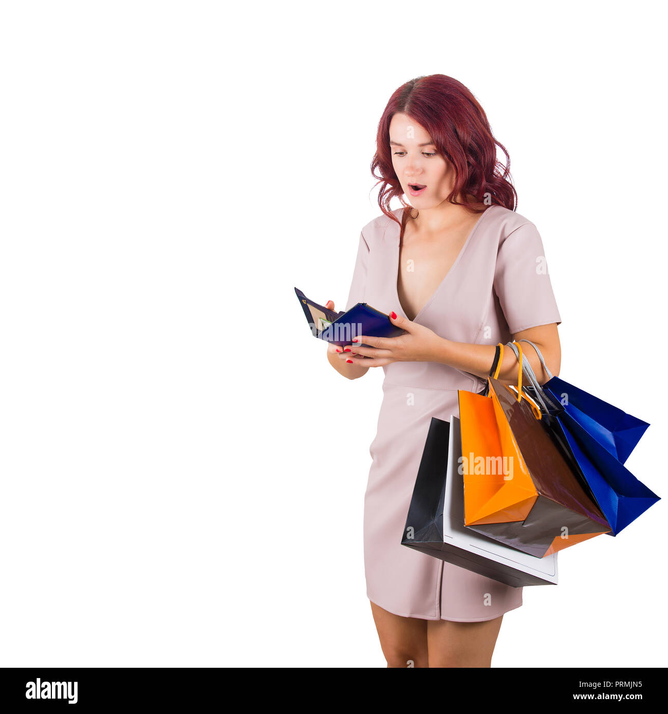 Shocked woman shopaholic carrying bags holding a empty wallet, has no money for shopping in her pouch isolated over white background. - Stock Image