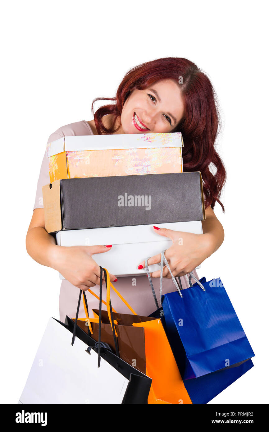 Excited young woman after shopping hugging boxes and bags she bought isolated over white background. - Stock Image