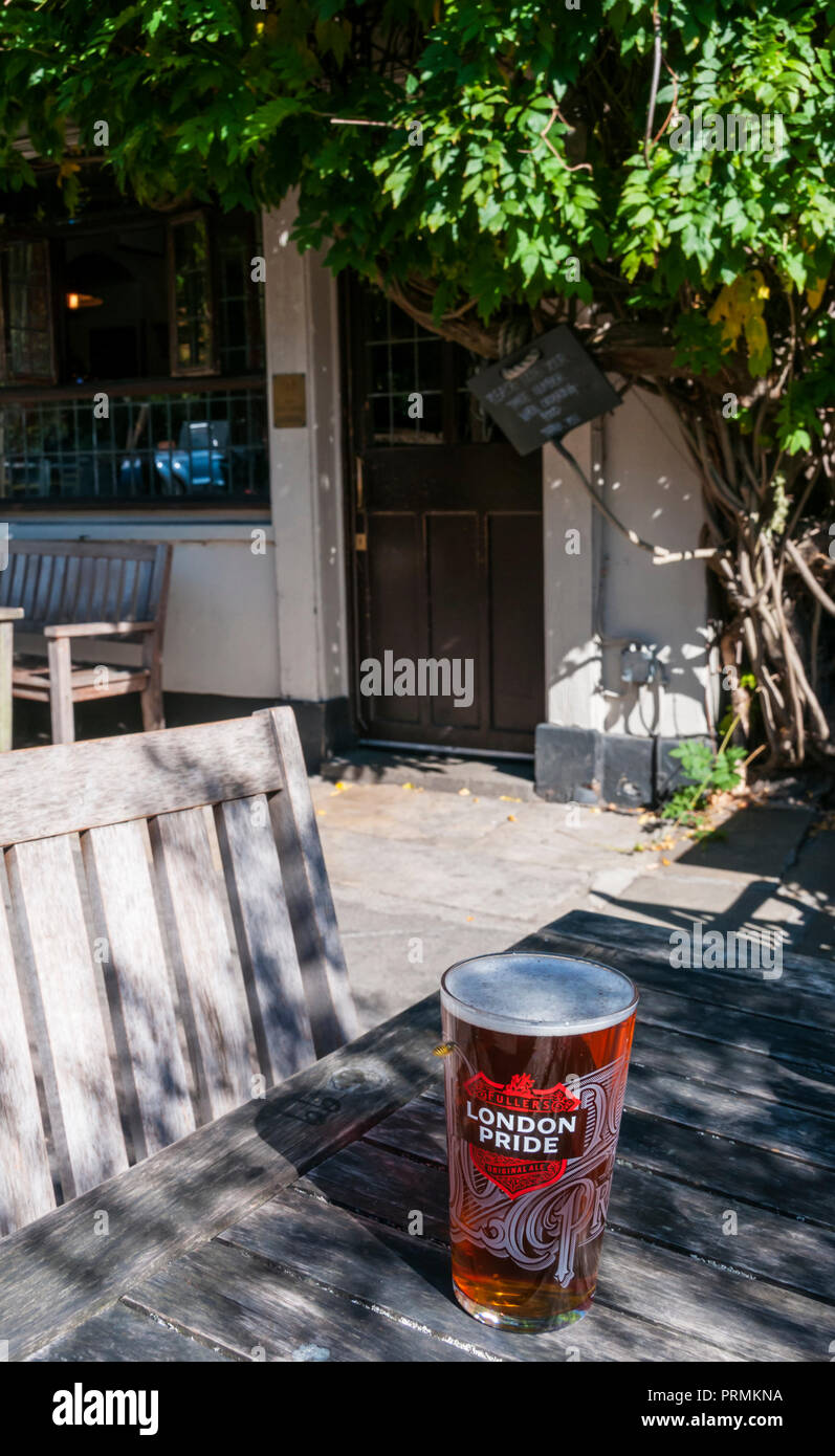 A pint of Fullers London Pride beer on a table outside the Flask public house in Highgate, North London. - Stock Image