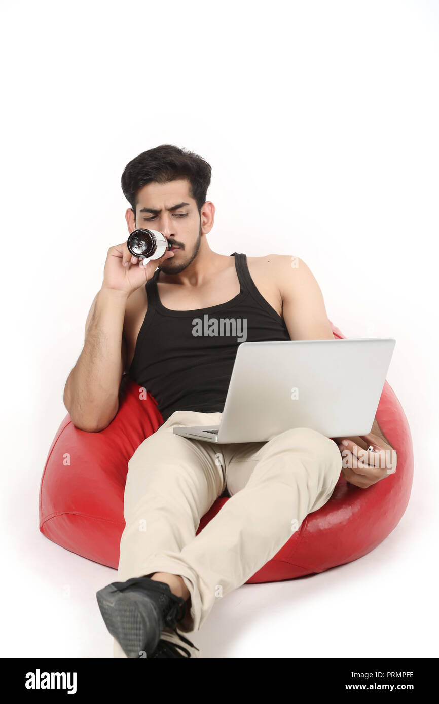 Handsome boy on the bean bag couch is drinking juice with looking laptop. Isolated on white background. - Stock Image