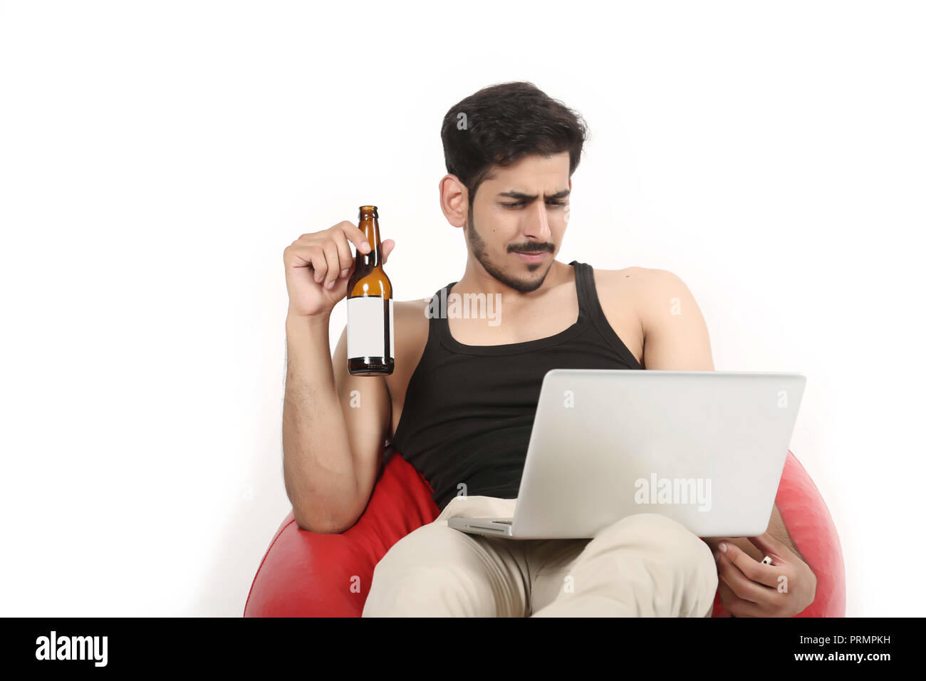 Portrait of Handsome boy on sitting bean bag couch is looking laptop with juice bottle. Isolated on white background. - Stock Image