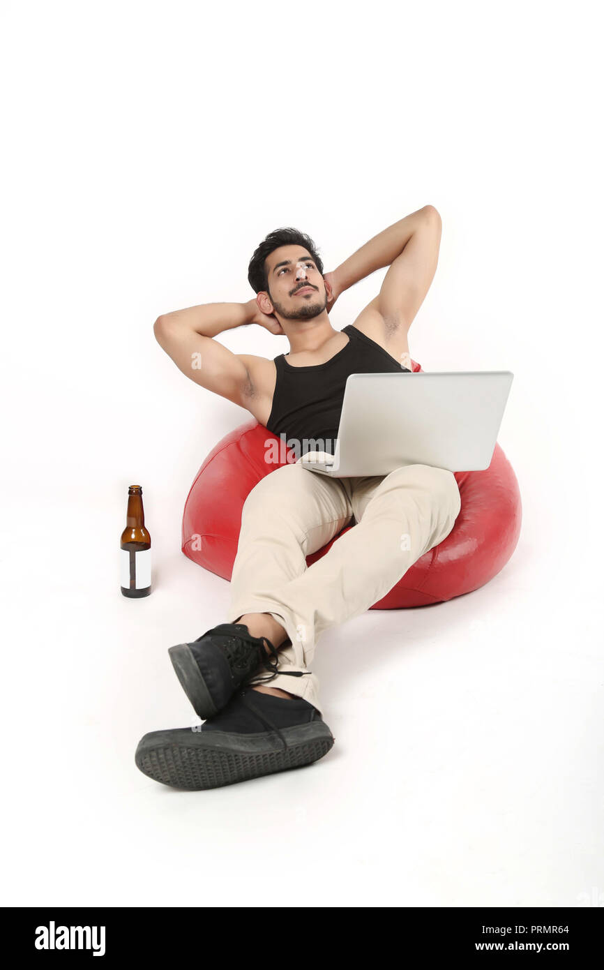 Young boy thinking on bean bag couch with laptop and juice bottle. Isolated on white background. - Stock Image