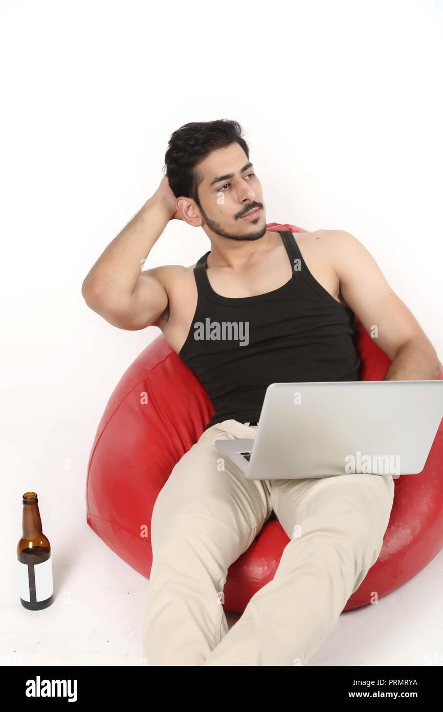Handsome boy sitting on the red bean bag couch with laptop and juice bottle. Isolated on white background. - Stock Image