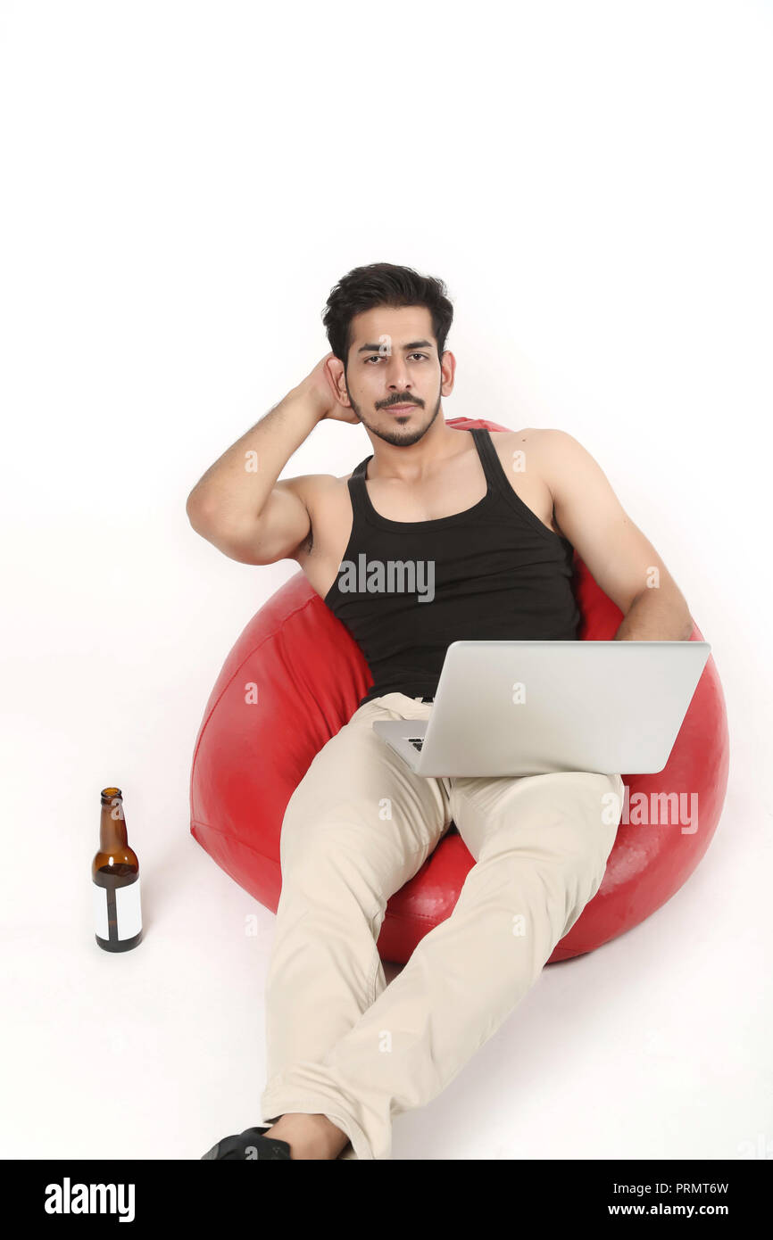 Picture of smart boy sitting on the red bean bag couch with laptop and juice bottle. Isolated on white background. - Stock Image