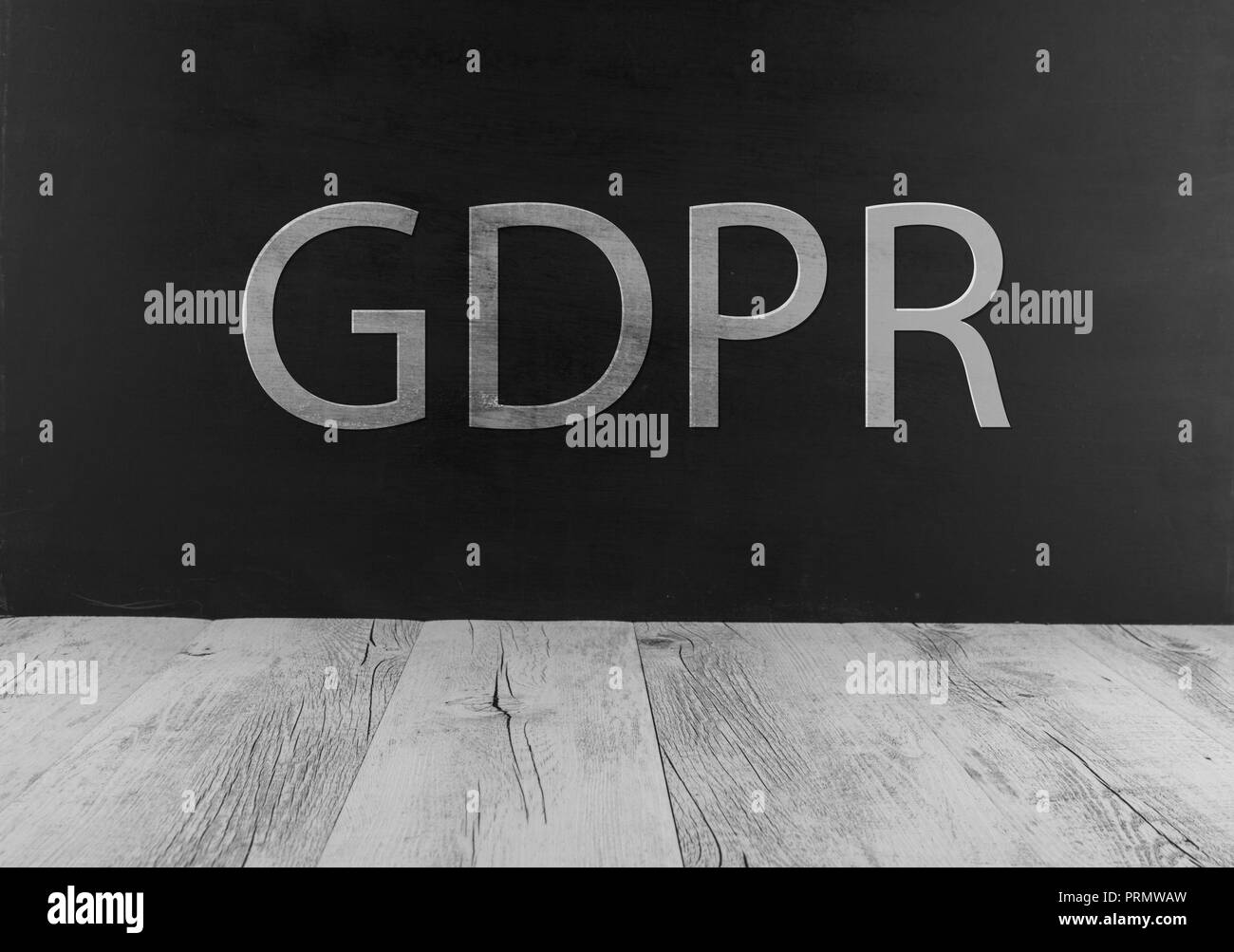GDPR - written on chalkboard black background above white rustic table - Stock Image