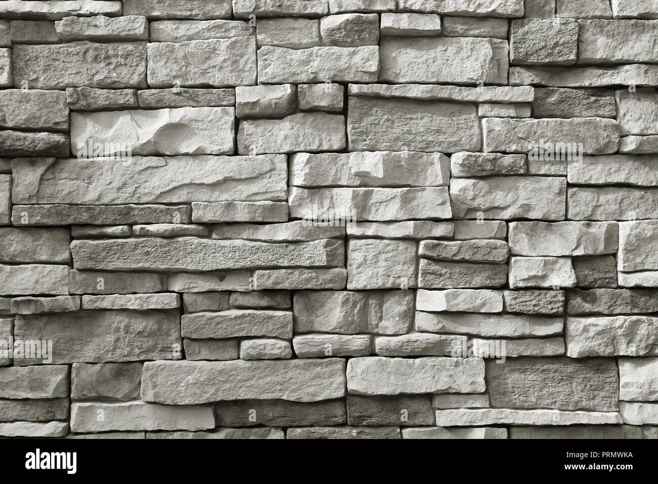 Front view of monotone grey rough stone wall for background or banner - Stock Image