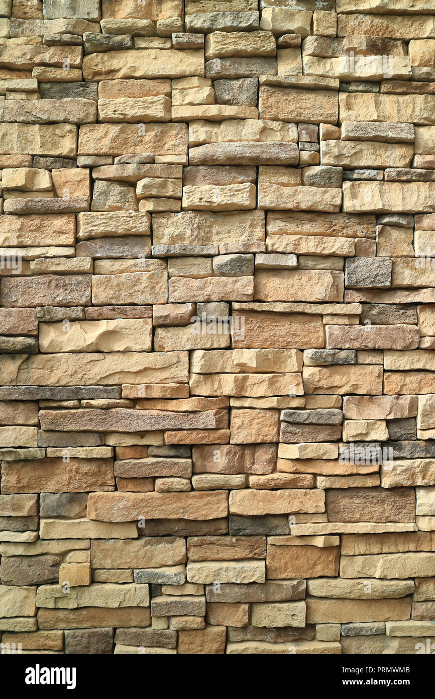 Vertical photo of brown and gray rough stone wall for background or banner - Stock Image