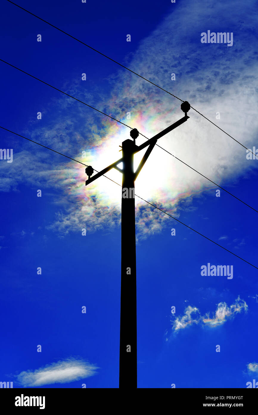 power comms cables and support pole against deep blue sky and three