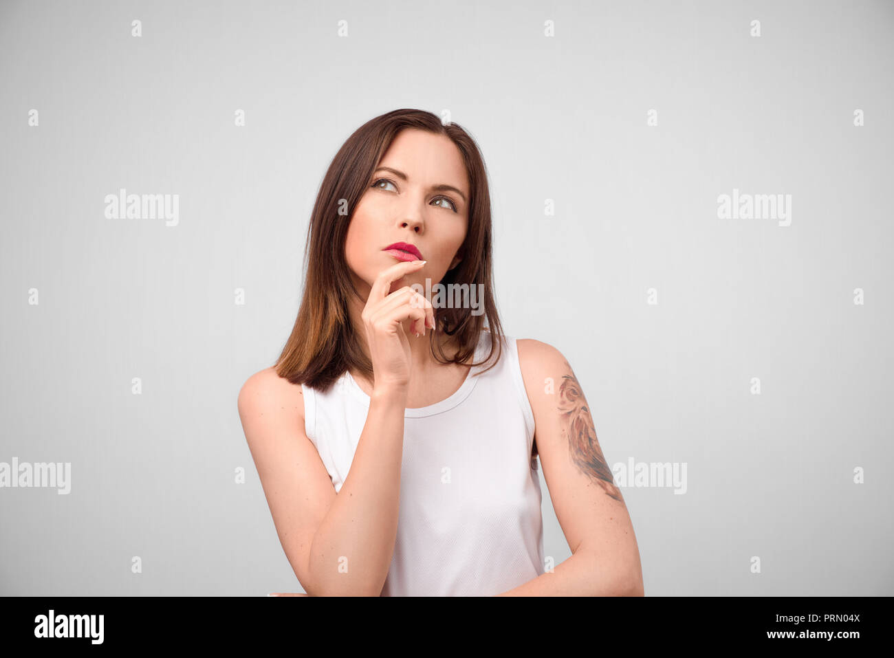 Beautiful brunette female with puzzled expression, keeps finger on lips, looks aside with bewilderment, poses against gray background. Body language a - Stock Image