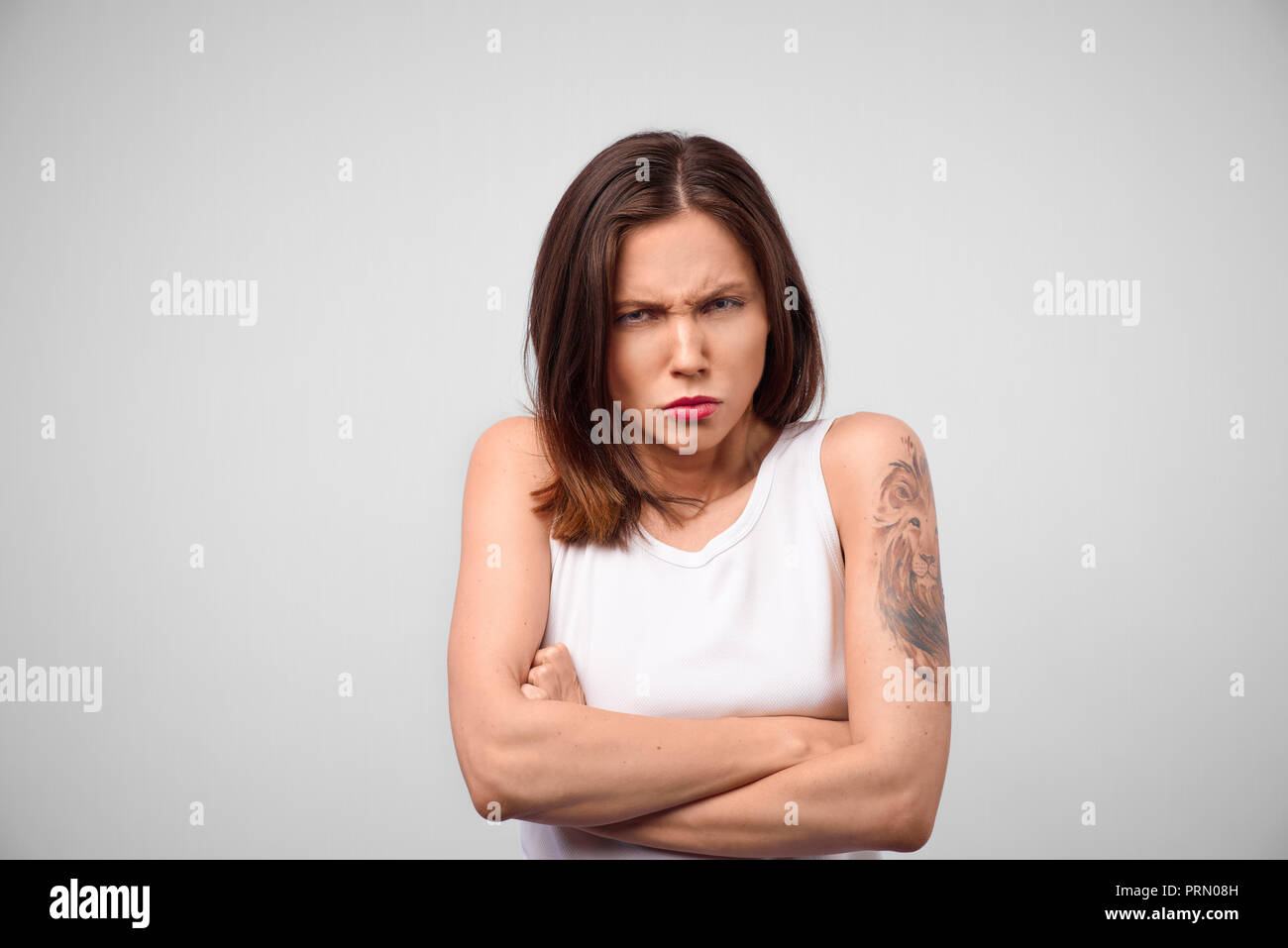 Angry annoyed young housewife keeping arms crossed and staring at camera with sceptical and distrustful look, feeling mad at someone. Human facial exp - Stock Image