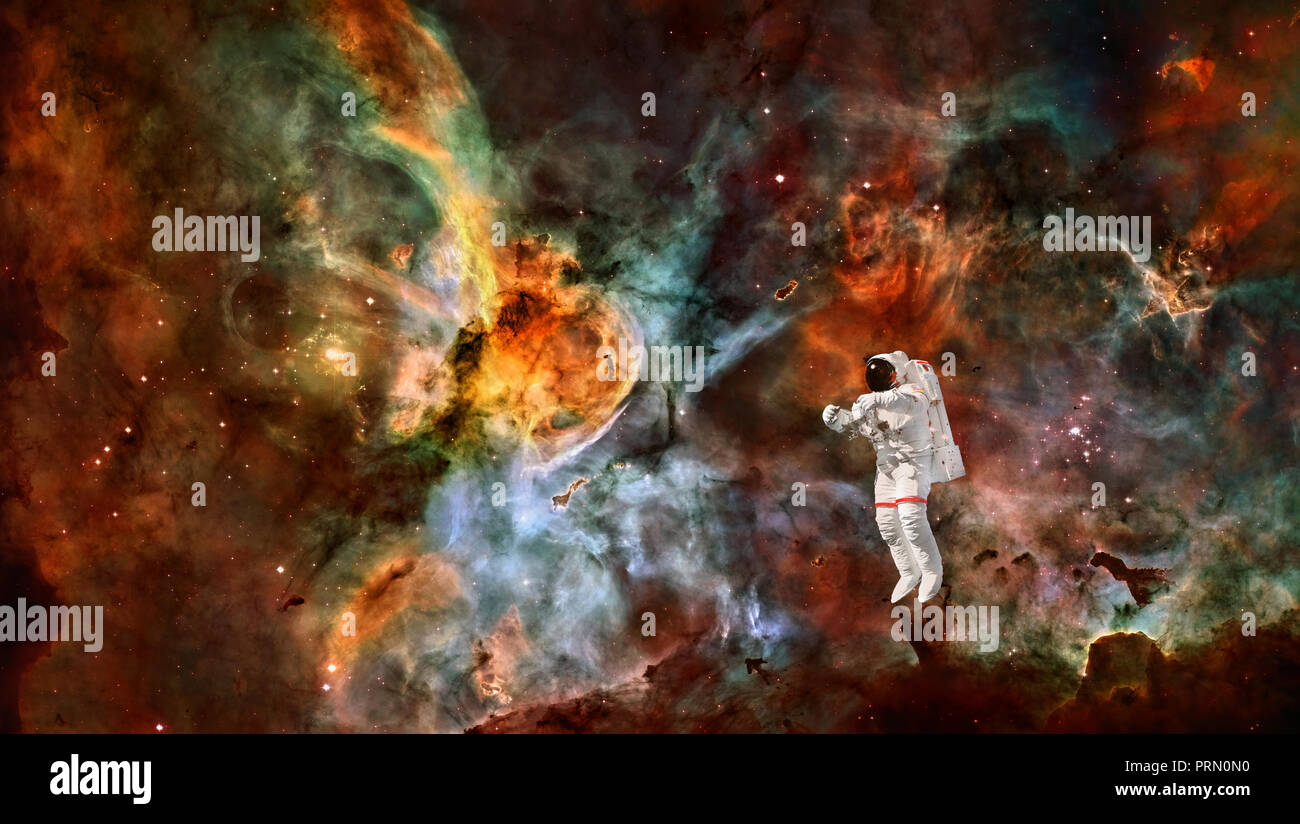 Astronaut in spacesuit floating in outer space. Spaceman in the universe. Space nebula. Elements of this image furnished by NASA - Stock Image