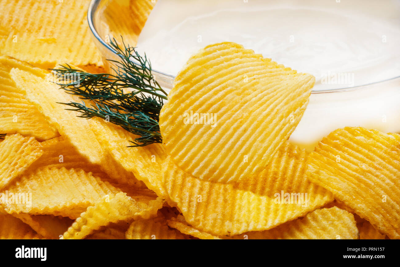 Potato chips close-up with bowl with sour cream and herbs. Macro. Food background Stock Photo