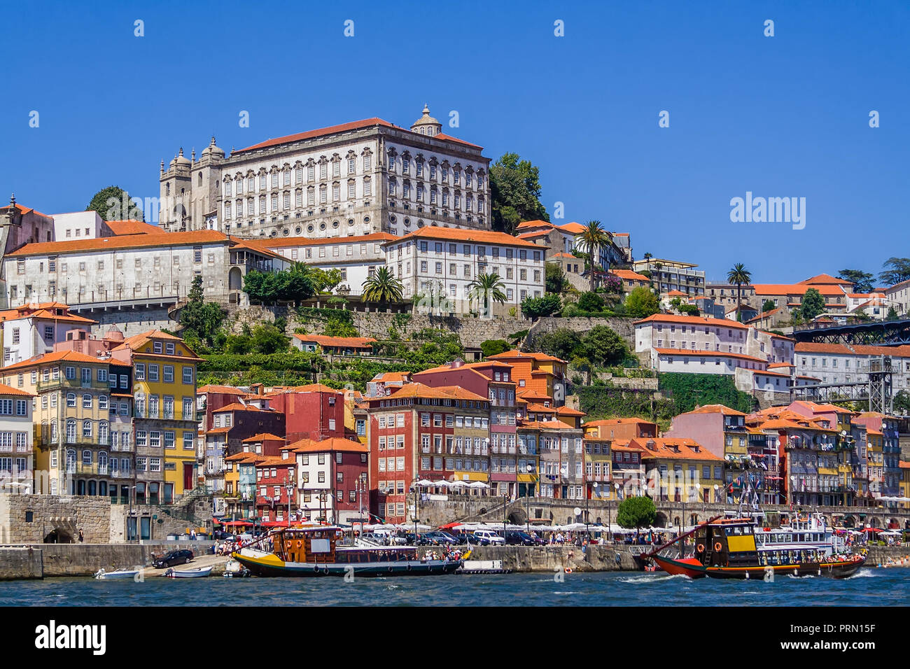Porto or Oporto, Portugal. Ribeira District with typical colorful buildings, the Douro River and cruise ships for tourists in of Rabelo boats shape - Stock Image