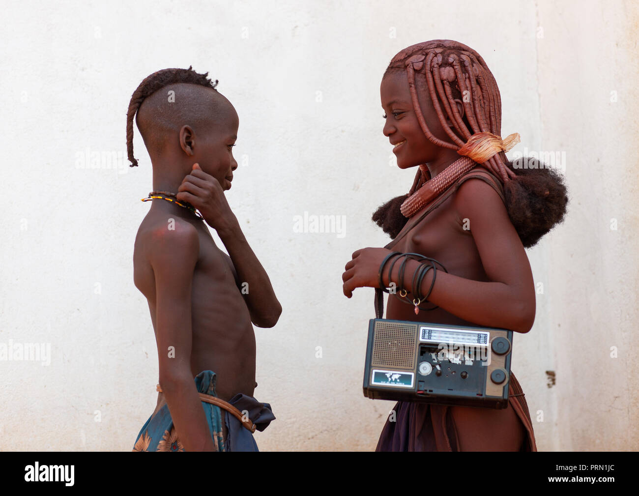 Himba tribe children with an audio tape recorder, Cunene Province, Oncocua, Angola - Stock Image