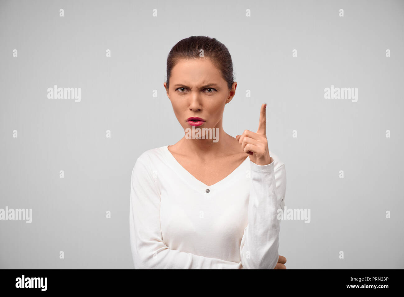 Portrait of unhappy Caucasian brunette woman boss having mad expression pointing her index finger up, looking angry and frowning. Serious female with  - Stock Image