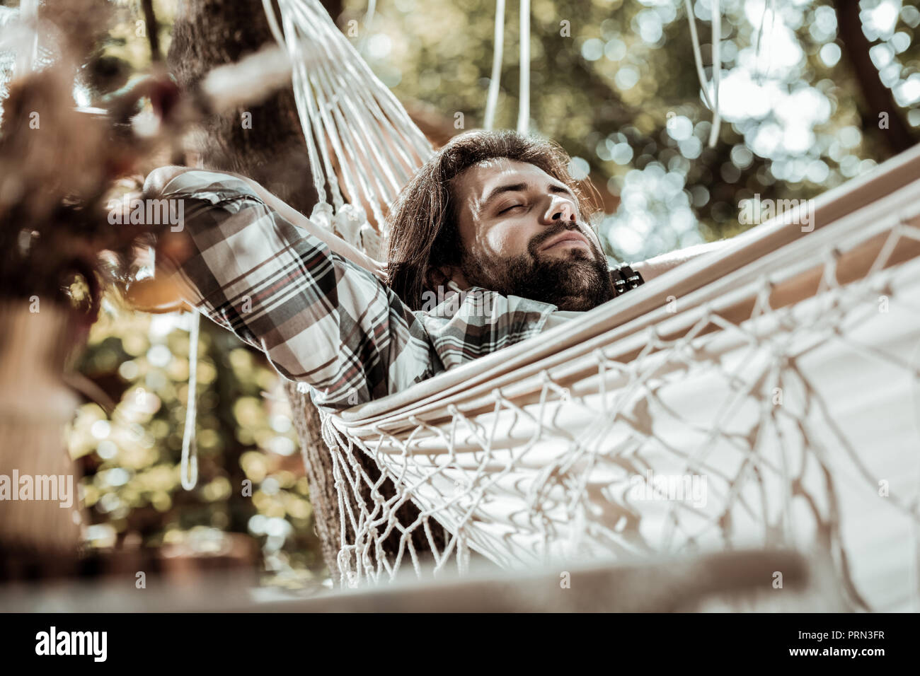 Handsome man dreaming about something in a hammock - Stock Image