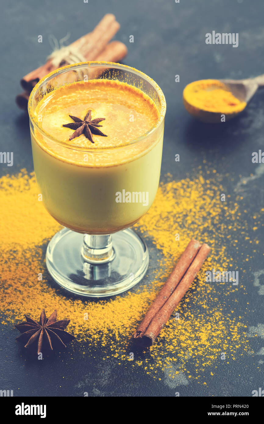 Golden Milk, a traditional Indian drink with turmeric powder. Warming drink against colds and flu. Antioxidant drink with spices. Selective focus - Stock Image