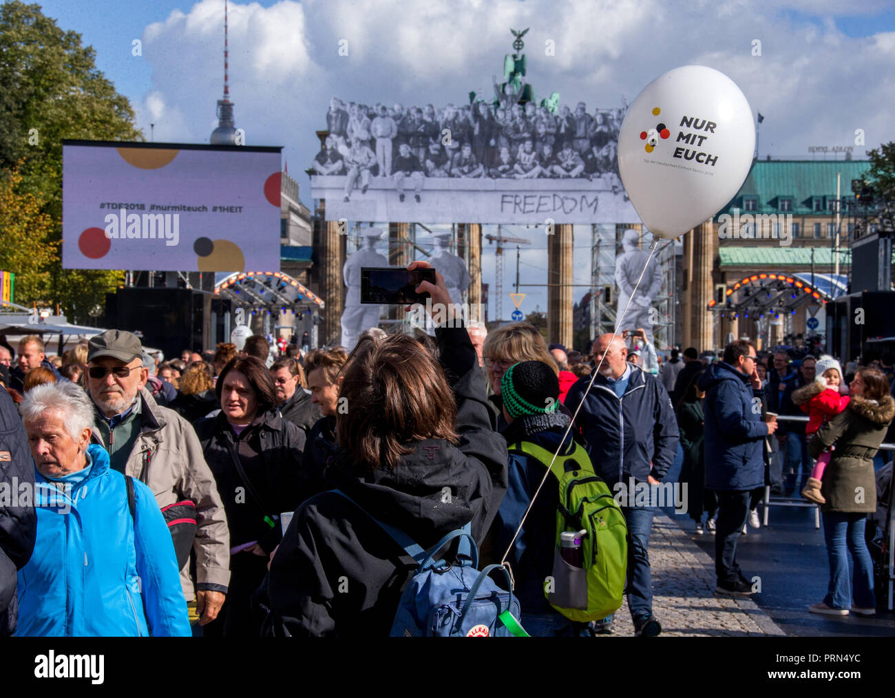 03 October 2018, Berlin: A visitor of the Citizens' Festival for the Day of German Unity photographs the Brandenburg Gate with historical photos from the day the Wall was opened. The motto of the three-day festival is 'Only with you'. Photo: Jens Büttner/dpa-Zentralbild/dpa - Stock Image