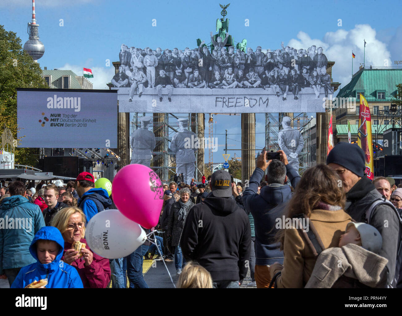 03 October 2018, Berlin: Visitors to the Citizens' Festival on German Unity Day take photographs of the Brandenburg Gate with historical photos of the opening of the Wall. The motto of the three-day festival is 'Only with you'. Photo: Jens Büttner/dpa-Zentralbild/dpa - Stock Image