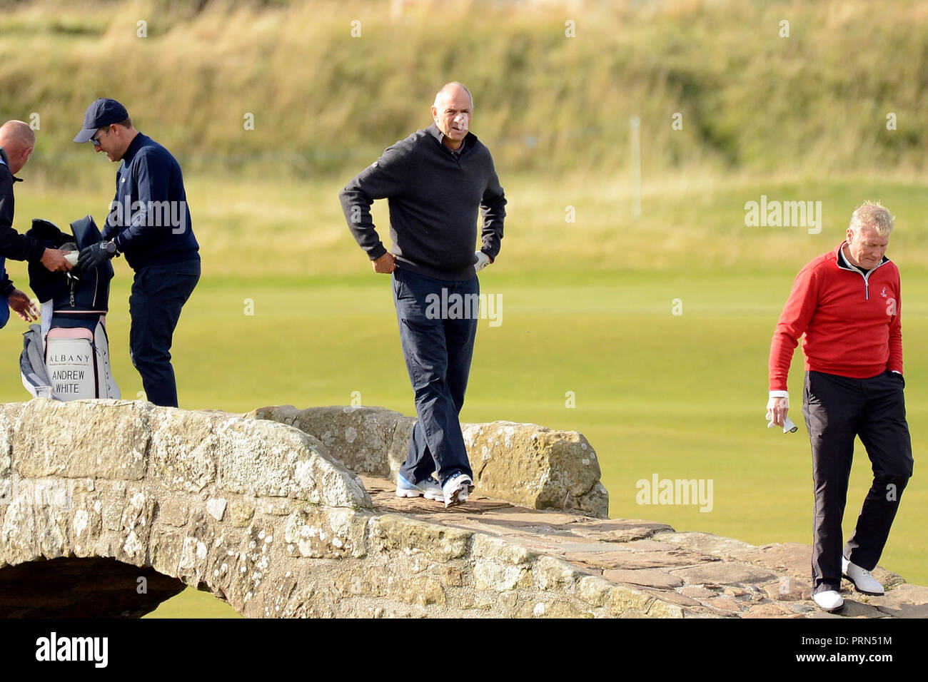 St Andrews, Scotland, United Kingdom, 03, October, 2018. Olympic rowing legend Sir Steve Redgrave (2nd R) crosses the famous Swilcan Bridge at the end of a practice round on the Old Course, St Andrews, before the start of the Dunhill Links Championship in which celebrity amateurs partner professional golfers in part of the event. © Ken Jack / Alamy Live News - Stock Image
