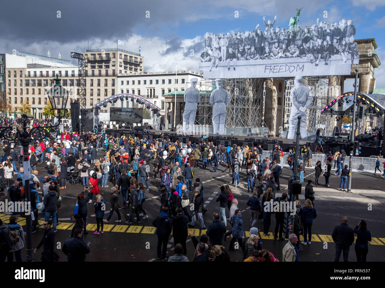 03 October 2018, Berlin: Visitors to the Citizens' Festival on German Unity Day pass by the Brandenburg Gate with historical photos of the day the Wall was opened. The motto of the three-day festival is 'Only with you'. Photo: Jens Büttner/dpa-Zentralbild/dpa - Stock Image