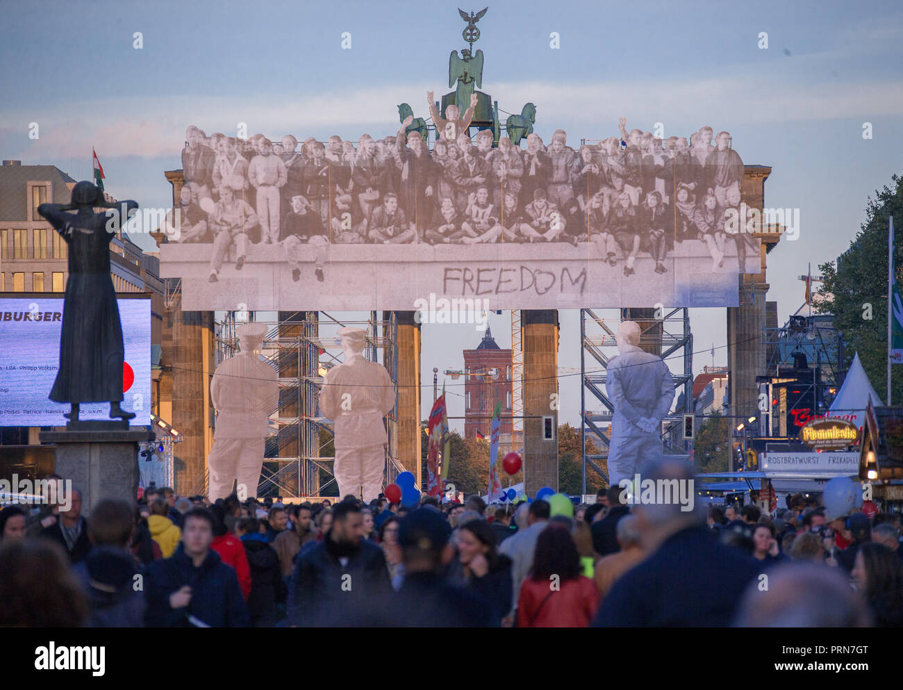 03 October 2018, Berlin: Shortly before sunset, visitors to the Citizens' Festival on German Unity Day pass by the Brandenburg Gate with historical photos of the day the Wall was opened. The motto of the three-day festival is 'Only with you'. Photo: Jens Büttner/dpa-Zentralbild/dpa - Stock Image